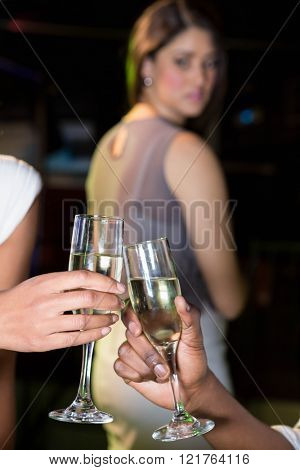 Couple toasting champagne glasses while unhappy looking at them in bar