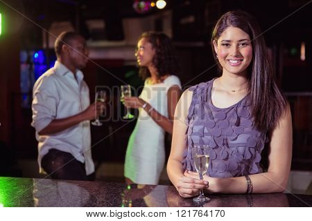 Young woman having champagne in bar while her friends having fun in background