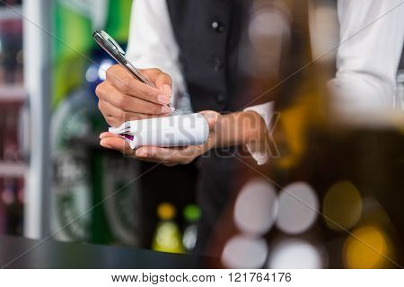 Waiter writing down an order in a bar