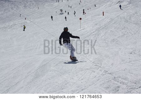 Young Snowboarder Woman Sliding Downhill.