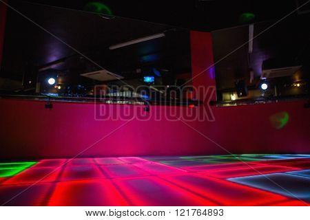 Red illuminated disco dance floor in bar