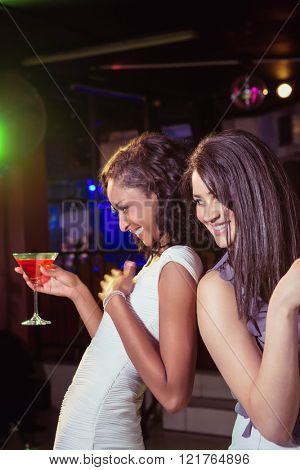 Happy young women having red cocktail in bar
