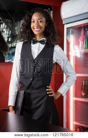 Portrait of bartender standing with a menu card in bar
