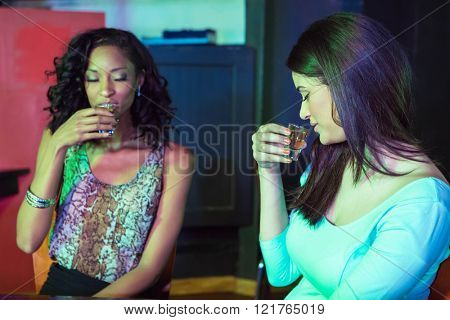 Two women having tequila at nightclub