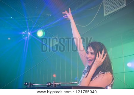 Pretty female DJ waving her hand while playing music at the nightclub