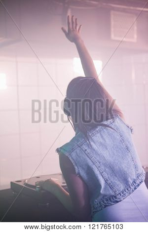 Female DJ waving her hand while playing music at the nightclub