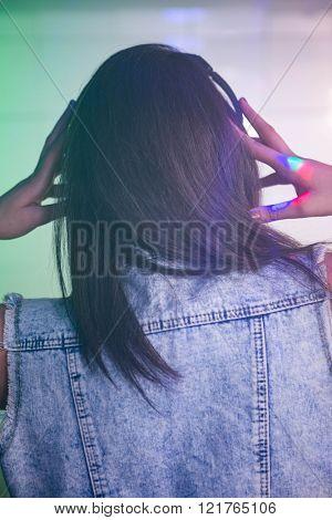 Female DJ listening music on headphone at nightclub