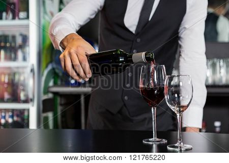 Mid section of bartender pouring red wine in a glass at bar counter