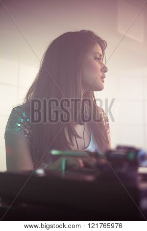 Pretty female DJ looking at audience while playing music at nightclub