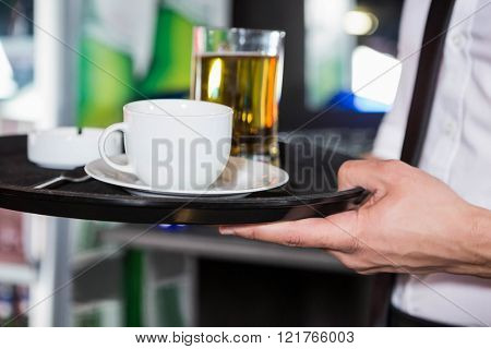 Waiter serving whiskey and a cup of coffee in bar