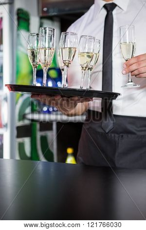 Mid section of bartender serving champagne in bar