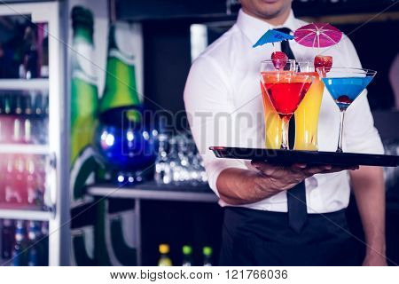 Mid section of bartender serving cocktail and martini at bar counter