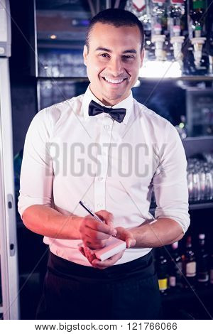 Portrait of a waiter writing down an order in a bar