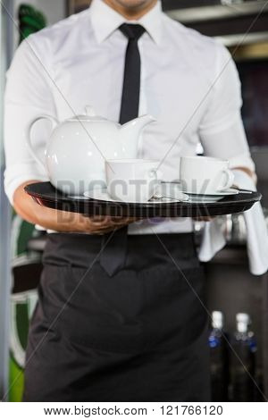 Mid section of waiter serving tea in bar