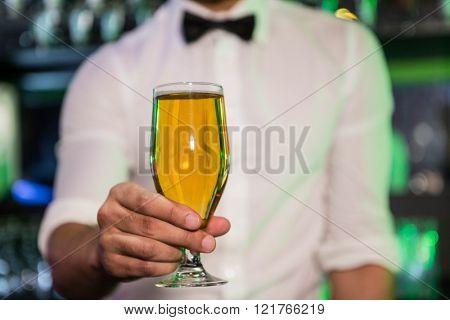Bartender serving a glass of beer in bar