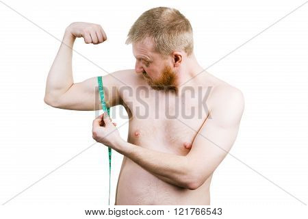 Frustrated bearded man measuring his biceps