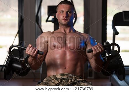 Bodybuilder Doing Exercise For Biceps With Machine