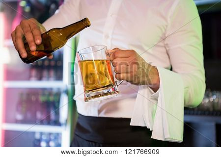 Bartender pouring beer in a pint in bar