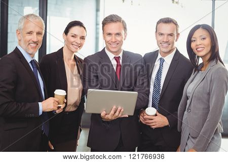 Portrait of businesspeople standing together with a laptop in office