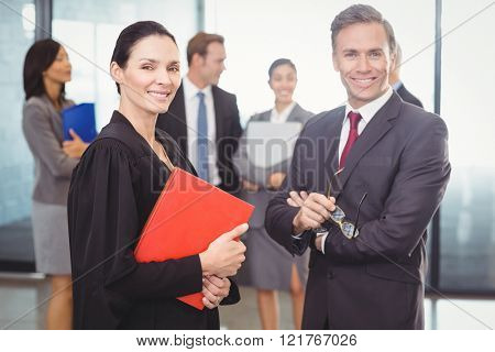 Portrait of businessman standing with lawyer in office