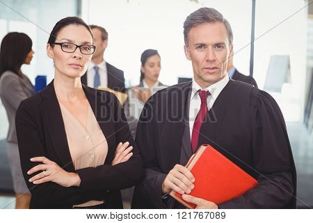 Portrait of businesswoman standing with lawyer in office
