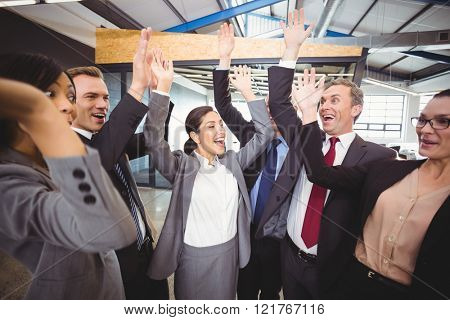 Cheerful businesspeople raising hands in office