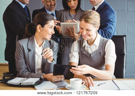Businesswomen using digital tablet and interacting in conference room