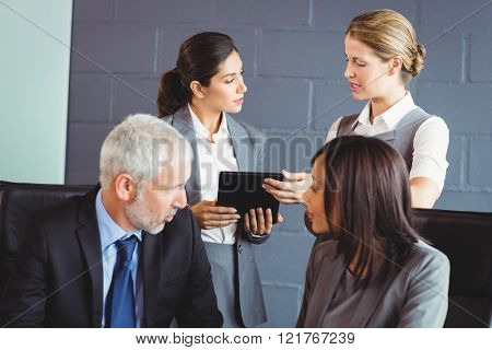 Businesspeople interacting in conference room in office