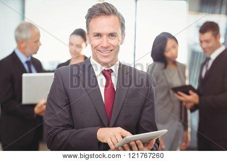 Portrait of businessman using digital tablet in office