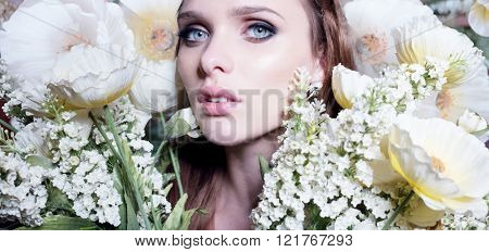 Beautiful portrait of a young woman surrounded by yellow flowers
