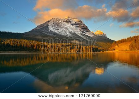 Mountain lake with reflection and fog at sunset in Banff National Park, Canada.