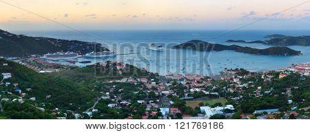 Virgin Islands St Thomas sunrise panorama with colorful cloud, buildings and beach coastline.