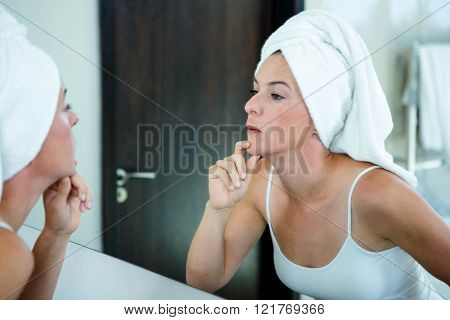 woman wearing a towel on her hair is inspecting her skin in a mirror