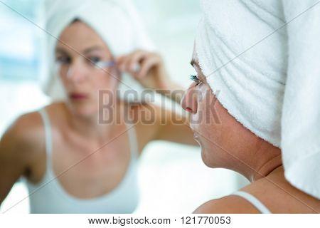 woman wearing a towel on her head, applying mascara