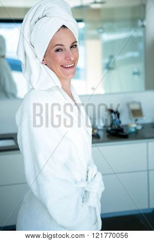 woman wearing a dressing gown and a towel on her head is smiling at the camera
