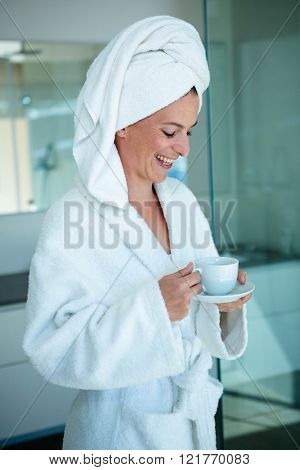 wooman in a dressing gown smiling and holding a cup and saucer