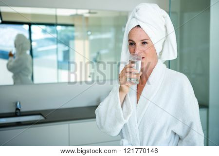 woman in a dressing gown with a towel on her head drinking a glass of water