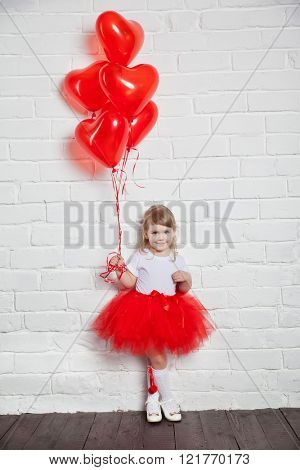 Little girl holding a heart-shaped ballon