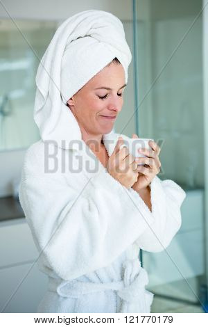 woman wearing a dressing gown and a towel on her head is smiling at the camera with a cup and saucer in her hand