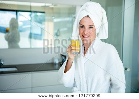 woman wearing a dressing gown and a towel on her head is drinking a glass of orange juice