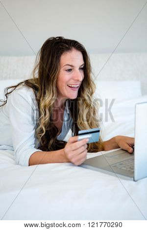 woman with brunette hair, lying on her stomach looking at her laptop annd holding her credit card