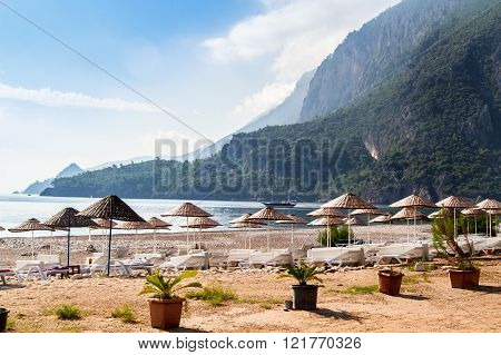 Deck Chairs Under Thatched Umbrellas On The Beach Of Ç?ral?.