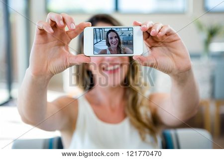 smiling woman sitting on the couch taking a selfie on her mobile phone