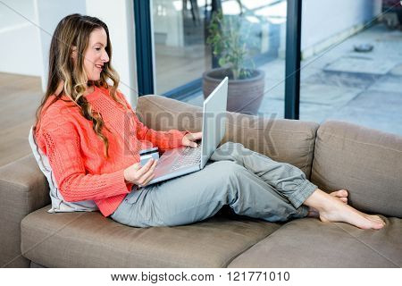 smiling woman lying on the couch on her laptop with her credit card