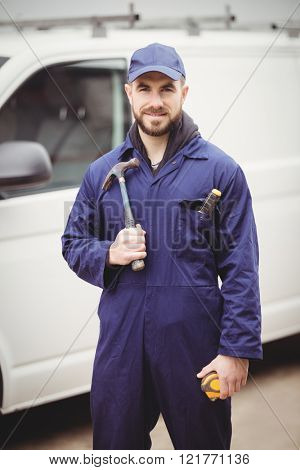Repairman holding a hammer in front of his van