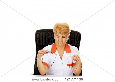 Worried elderly female doctor or nurse sitting behind the desk and holds two pair of glasses