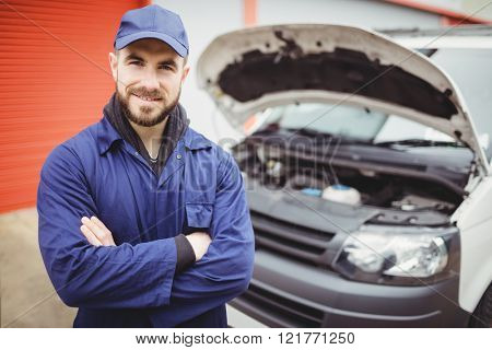 Mechanic with arms crossed standing in front of a van