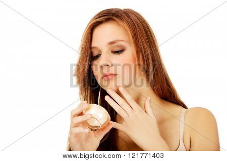 Happy young woman applying cream moisturizer