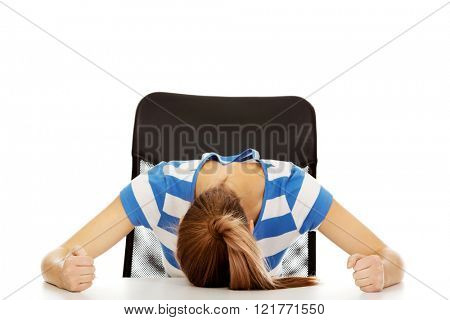 Worried teenage woman sleeping at the desk