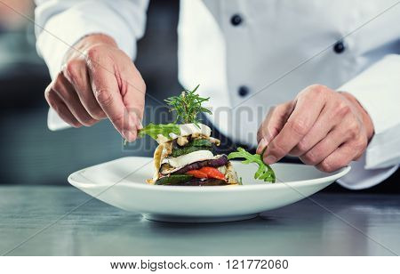 Chef in Restaurant garnishing vegetable dish, crop on hands, filtered image